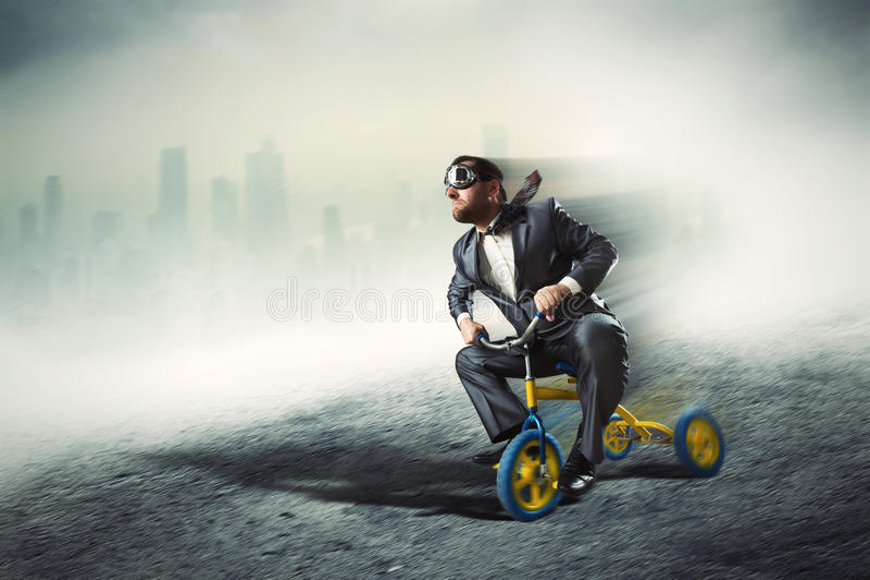 Nerdy affärsman som rider en liten cykel arkivbilder