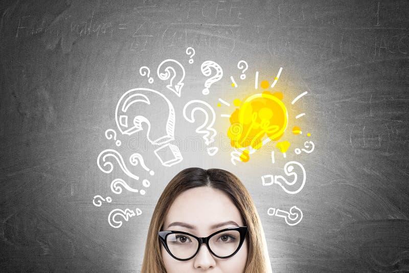 Nerdy asiatisches Mädchen und Glühlampe der Fragezeichen stockfoto