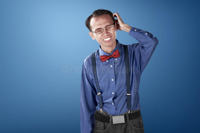 Nerdy business man confused with blue background. Dressed blue and bow tie with suspender royalty free stock photo
