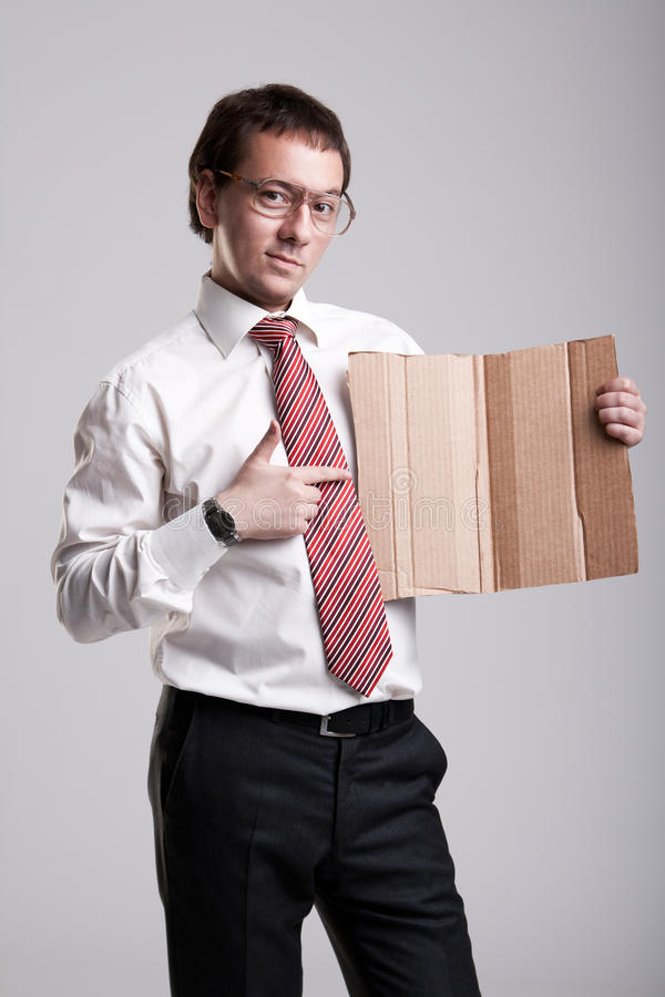 Nerdy businessman holding a cardboard.  royalty free stock photo
