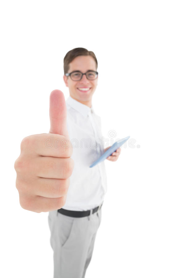 Nerdy businessman holding his digital tablet showing thumbs up. On white background stock photography