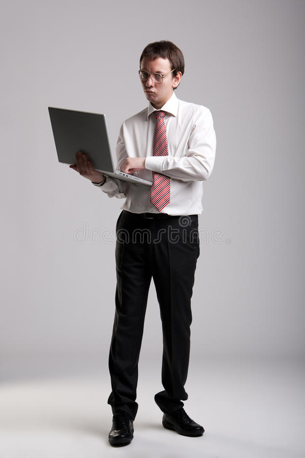 Nerdy businessman holding a laptop. And making a face royalty free stock image