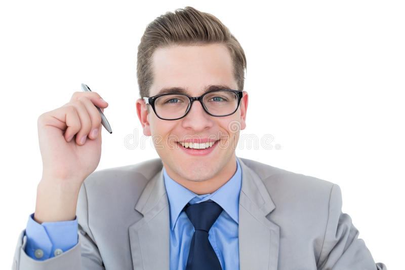 Nerdy businessman holding pen smiling at camera. On white background royalty free stock images