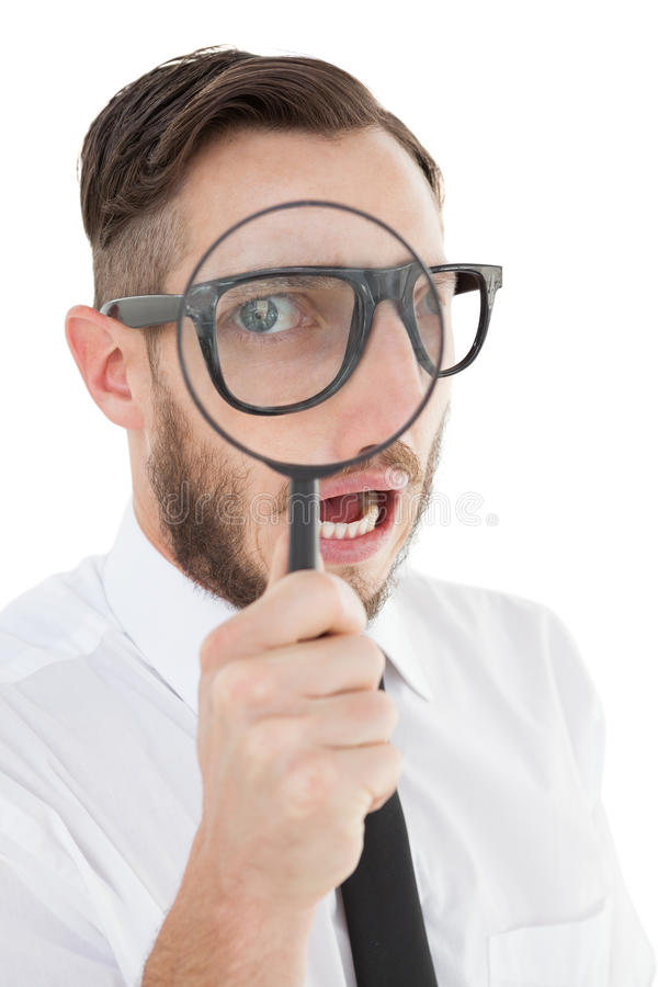 Nerdy businessman looking through magnifying glass. On white background royalty free stock photography