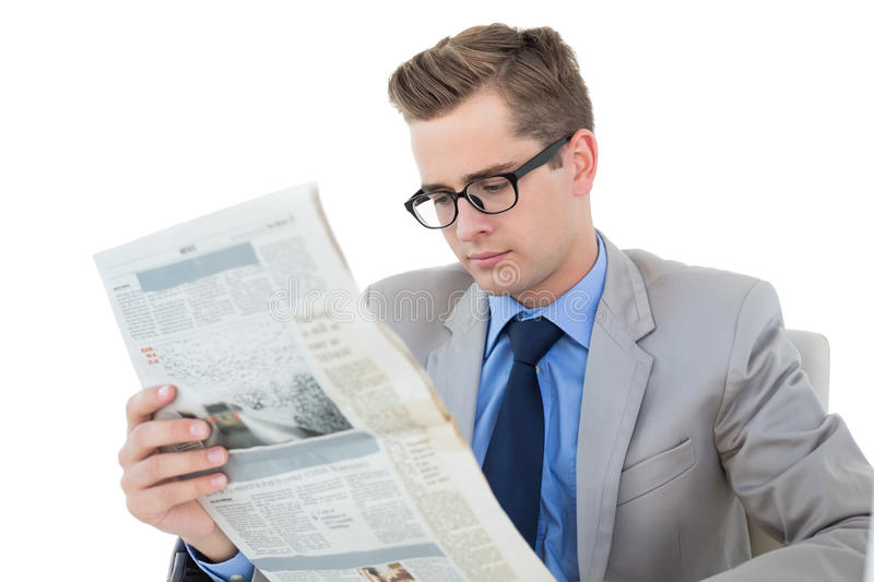 Nerdy businessman reading the newspaper. On white background royalty free stock image