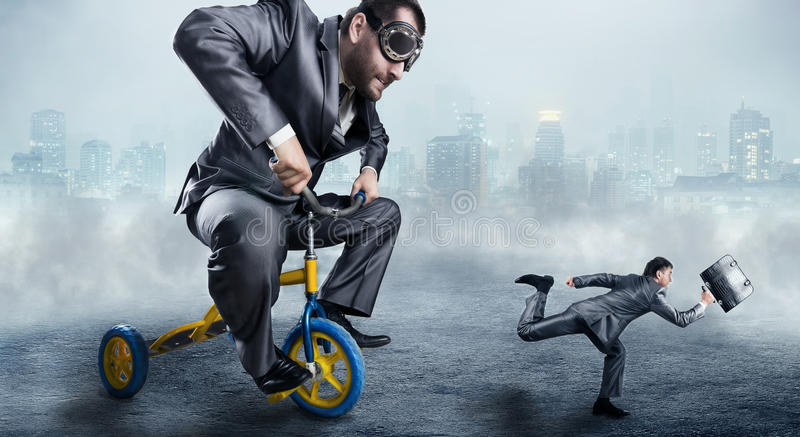 Nerdy businessman riding a small bicycle. And is trying to catch a small one stock photo