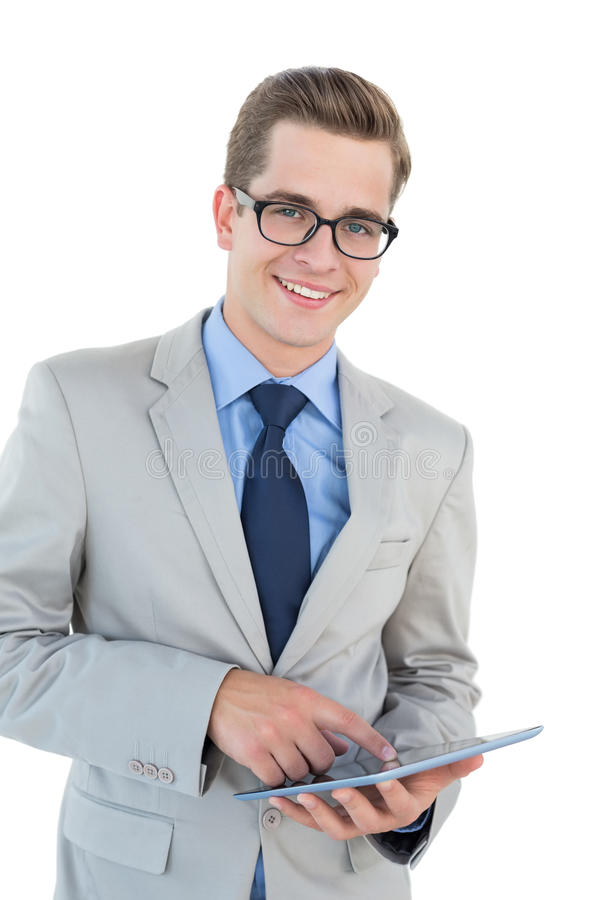 Nerdy businessman using his tablet pc. On white background stock photography
