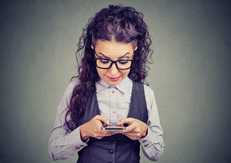 Nerdy flicka som använder en smart telefon royaltyfri bild