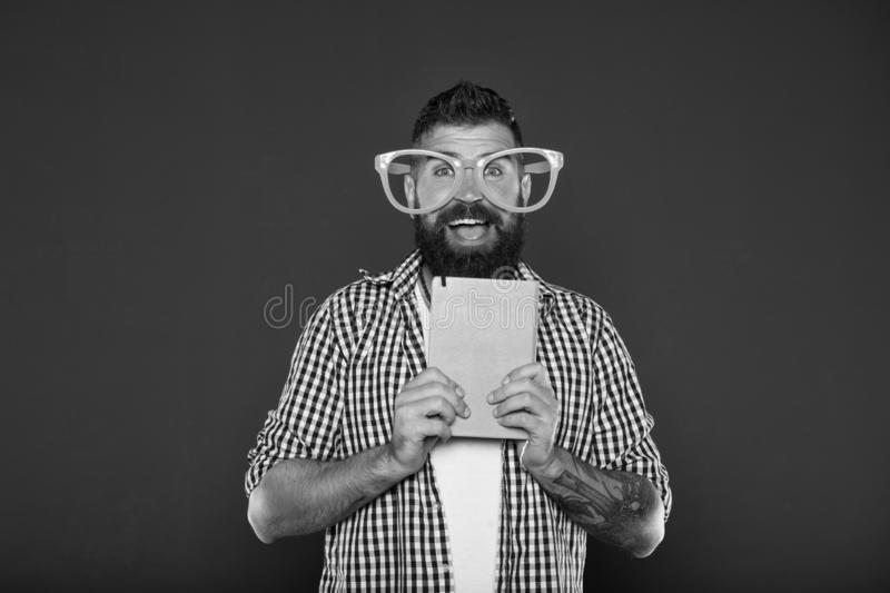 Nerdy and funny. University male student with lecture notes. Study nerd holding book. Book nerd wearing fancy glasses stock photo