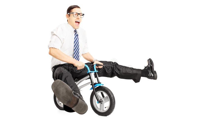 Nerdy jong mannetje met band die een kleine fiets berijden stock afbeelding
