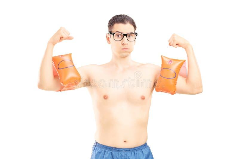 Nerdy jonge mens met zwemmende wapenbanden die zijn spieren tonen royalty-vrije stock fotografie