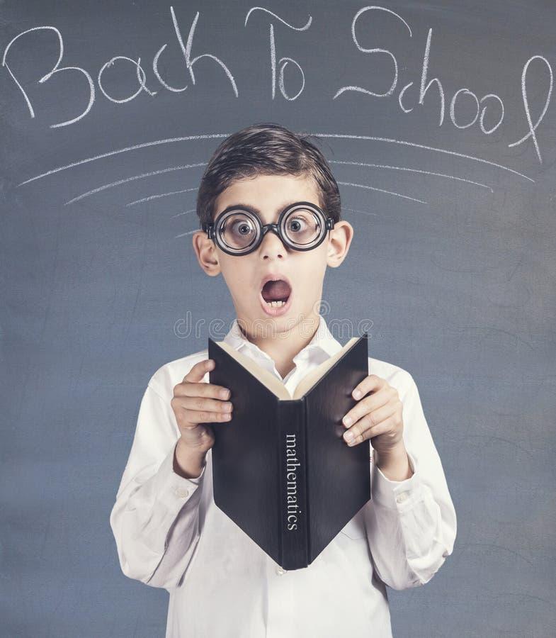 Nerdy liten skolapojke framme av en svart tavla royaltyfria foton