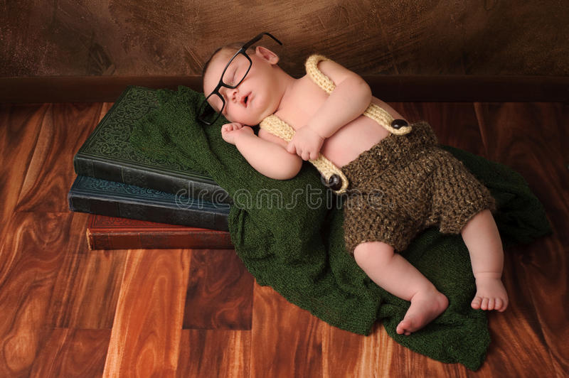 Nerdy Newborn Baby Boy. Ten day old newborn baby boy wearing crocheted shorts and suspenders. He has on adult reading glasses and is sleeping on a stack of royalty free stock photo