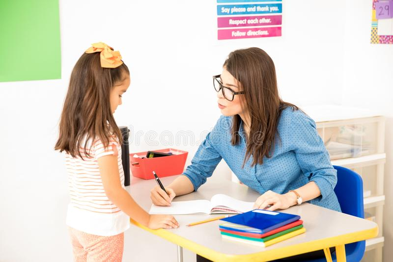 Teacher grading a student`s work. Nerdy preschool teacher wearing glasses and grading the work of one of her students while sitting in her desk royalty free stock photo