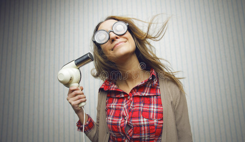 Nerdy woman drying hair stock photo
