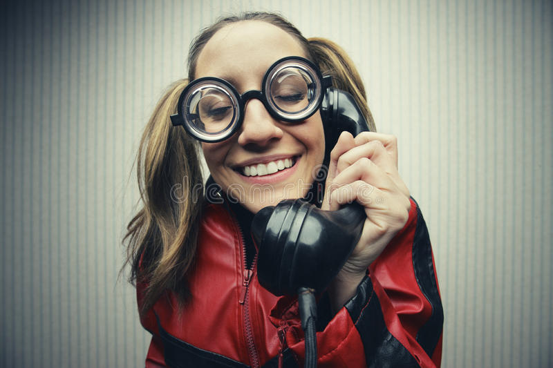 Nerdy woman speaking on a black rotary vintage phone stock image