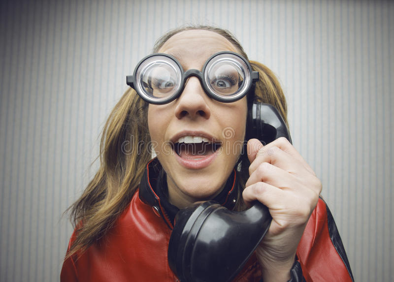 Nerdy woman speaking on a black rotary vintage phone royalty free stock photo