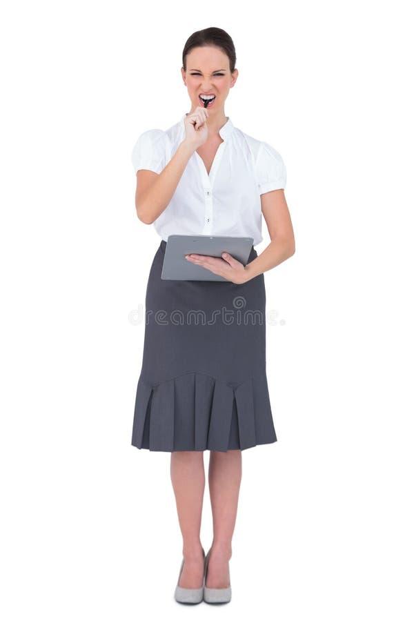 Nervös affärskvinna som biter hennes penna arkivbild