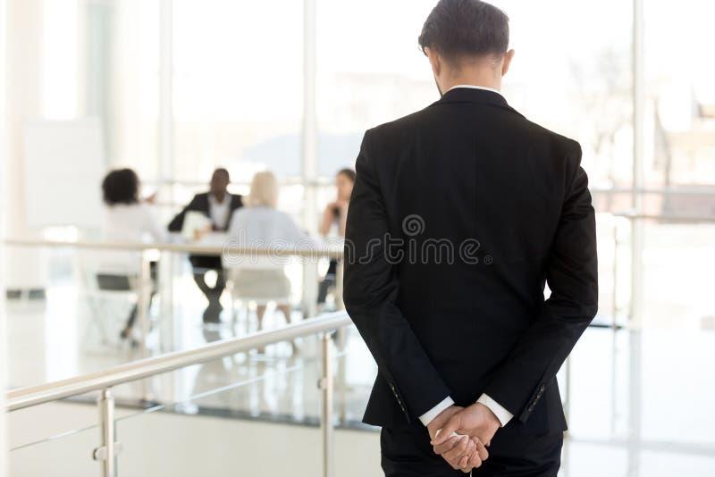 Nervös affärsman som väntar för att skriva in på den bakre sikten för affärsmöte royaltyfri bild