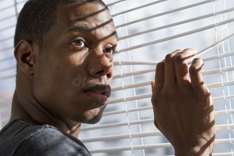 Nervös afrikansk amerikanman på fönstret som är horisontal royaltyfri bild