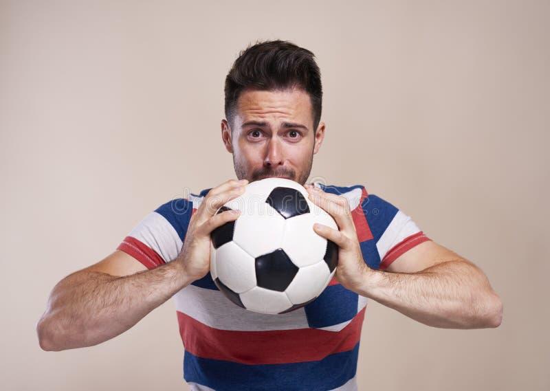 Nervös fotbollfan med fotbollbollen royaltyfria foton