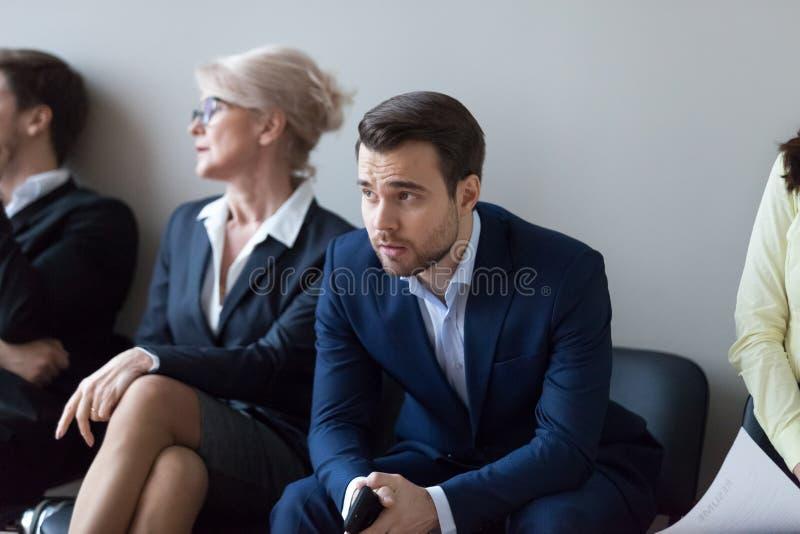 Nervös millennial manlig anställdväntan i köen för intervju royaltyfri bild