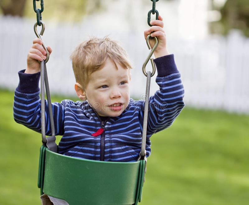 Nervös pojke på swing royaltyfria foton