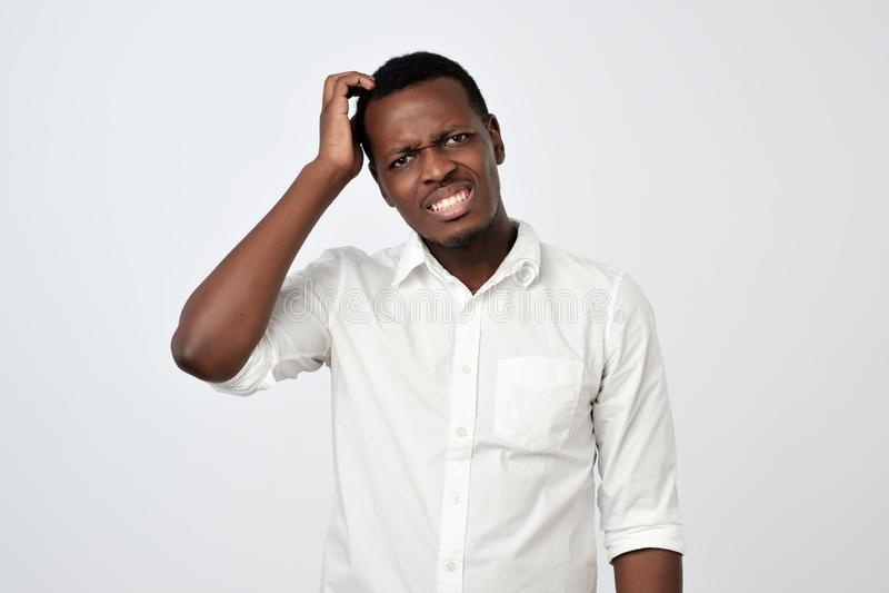 Nervös tvivelaktigt afrikansk man som har förbryllat blicken som går att göra allvarligt beslut royaltyfria foton