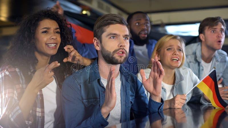 Nervöse Anhänger, die deutsche Flagge, aufpassendes Sportprogramm in der Stange, Hoffnung wellenartig bewegen lizenzfreies stockfoto