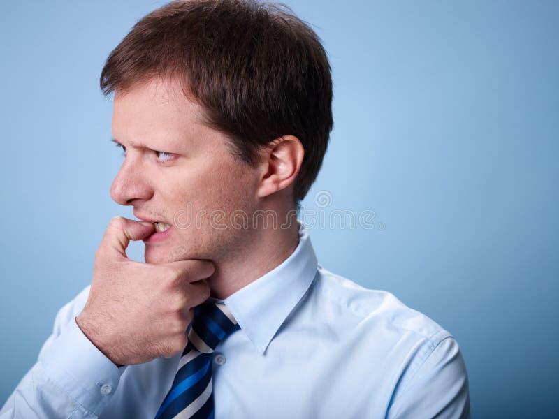 Nervöse beißende Fingernägel des Geschäftsmannes stockbilder