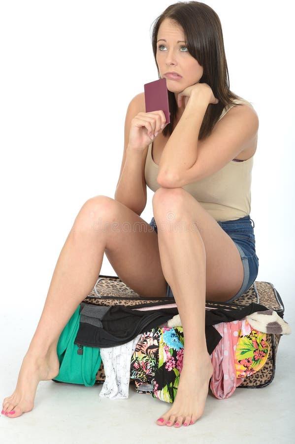 Nervöse besorgte junge Frau, die einen Pass sitzt auf einem überfließenden Koffer hält lizenzfreies stockfoto