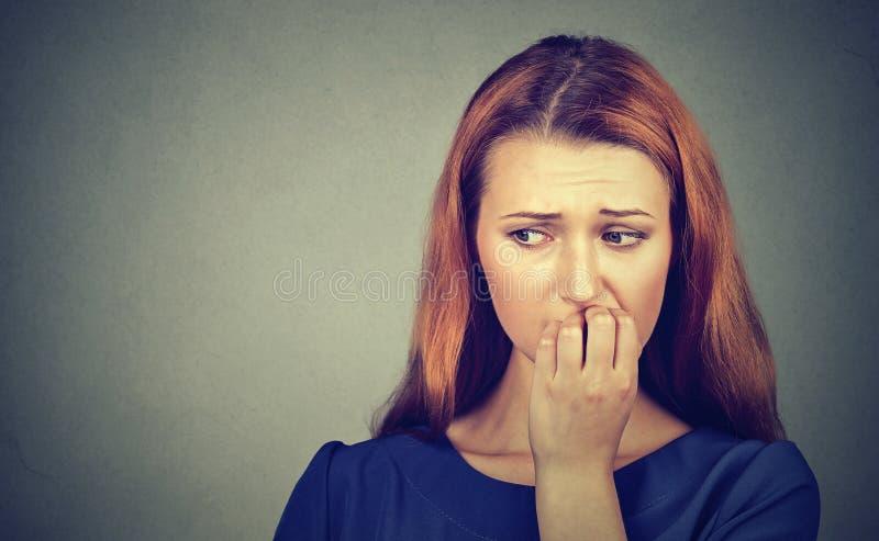Nervöse Frau, die ihre Fingernägel sich sehnen etwas beißen oder besorgt stockbild