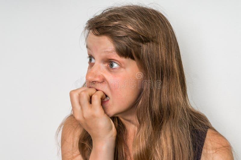 Nervöse Frau, die ihre Nägel beißt stockfoto