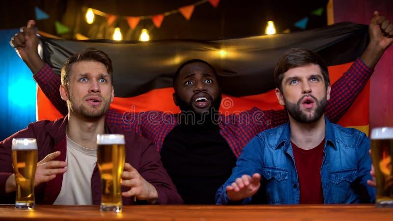 Nervöse männliche Fans mit aufpassendem Spiel der deutschen Flagge und Unterstützungsfußballteam lizenzfreie stockbilder