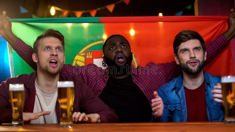 Nervöse portugiesische Fans, die auf entscheidenden Tritt für Fußballteamsieg, Flagge warten stockbild