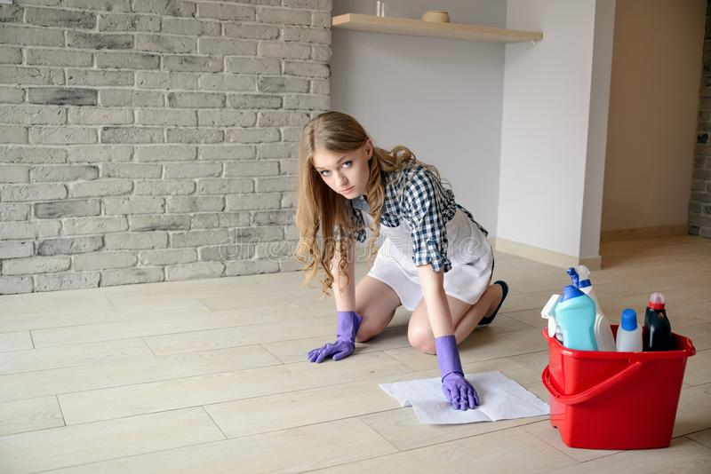 Nervöse und müde schöne junge Frau wäscht den Boden auf ihren Knien stockfoto
