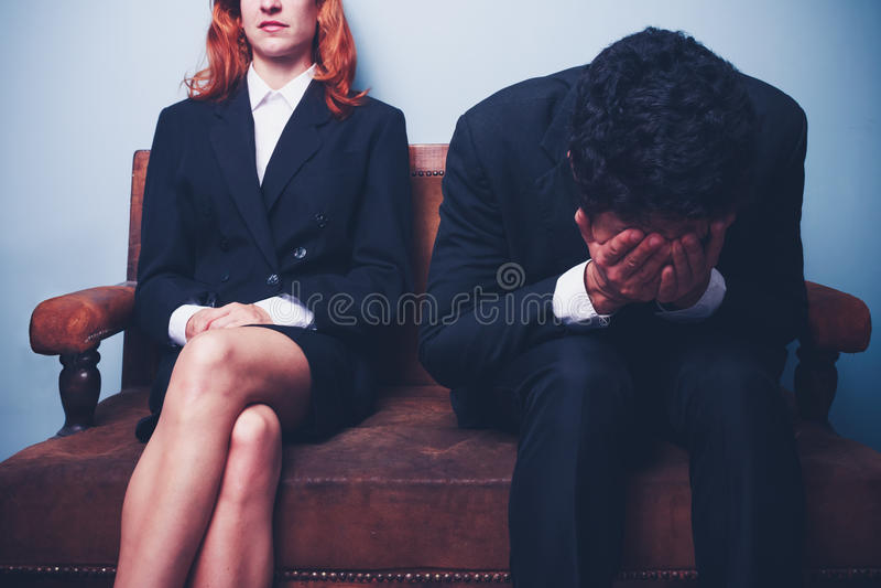 Nervöser Geschäftsmann, der nahe bei überzeugter Geschäftsfrau sitzt lizenzfreies stockbild