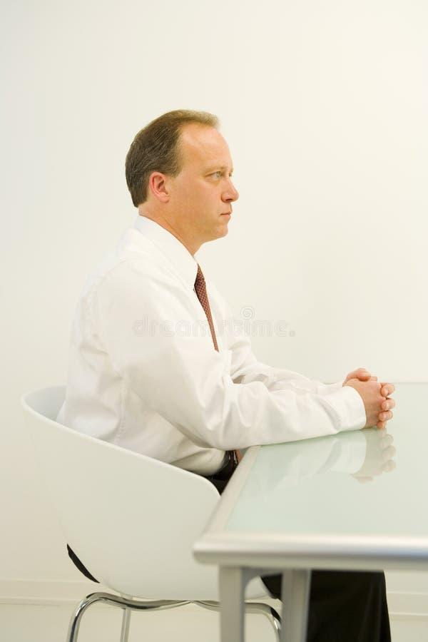Nervöser Geschäftsmann am Schreibtisch lizenzfreies stockfoto