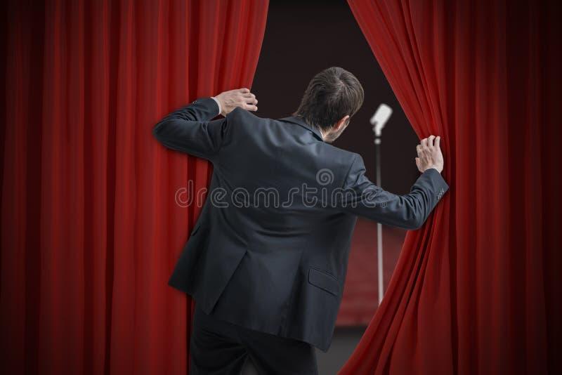 Nervöser Mann hat vor allgemeiner Rede Angst und versteckt sich hinter Vorhang lizenzfreie stockfotos