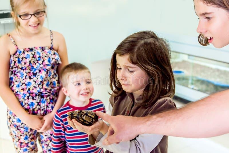 Nervöses Mädchen hält Schlange lizenzfreie stockfotografie