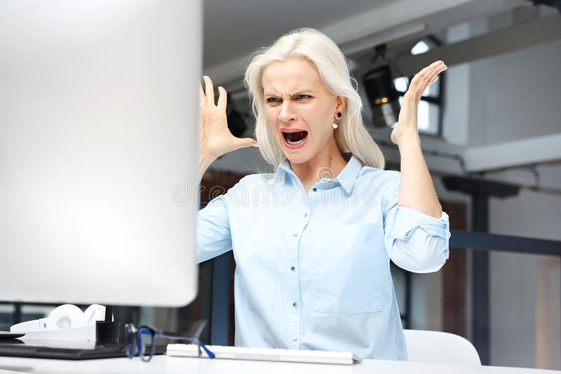 Nerves and anger at work. Furious young woman is irritated at work royalty free stock photography