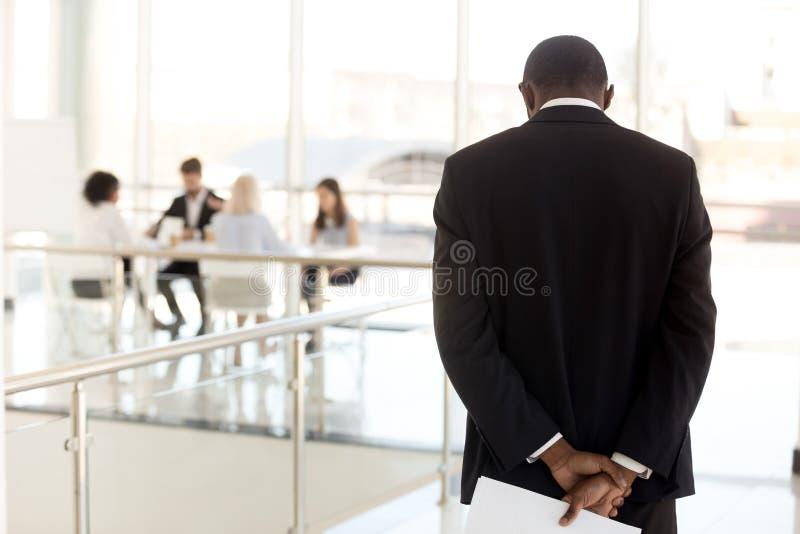 Nervous black employee waiting in hallway before entering meetin. Nervous African American employee standing in hallway waiting to enter business meeting royalty free stock image