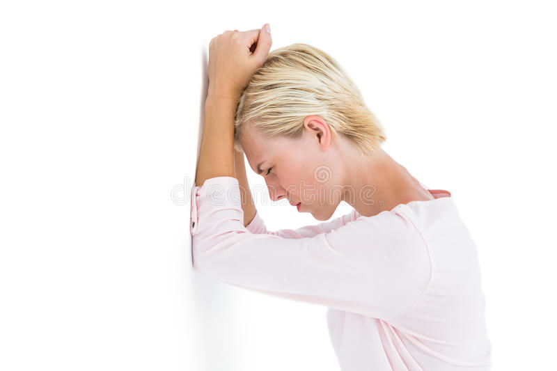Nervous blonde woman leaning against the wall stock image