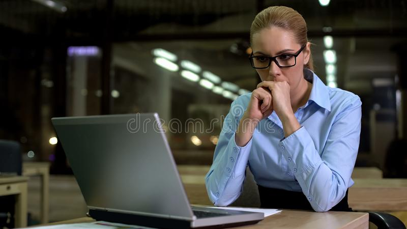 Nervous business woman looking at laptop, afraid of work failure and bad news royalty free stock photos