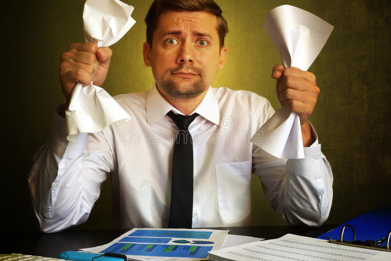 Nervous businessman observing bills. royalty free stock photos