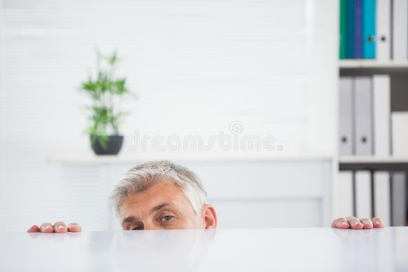 Nervous businessman peeking over desk royalty free stock photo