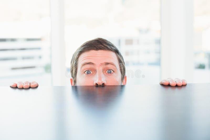 Nervous businessman peeking over desk stock image