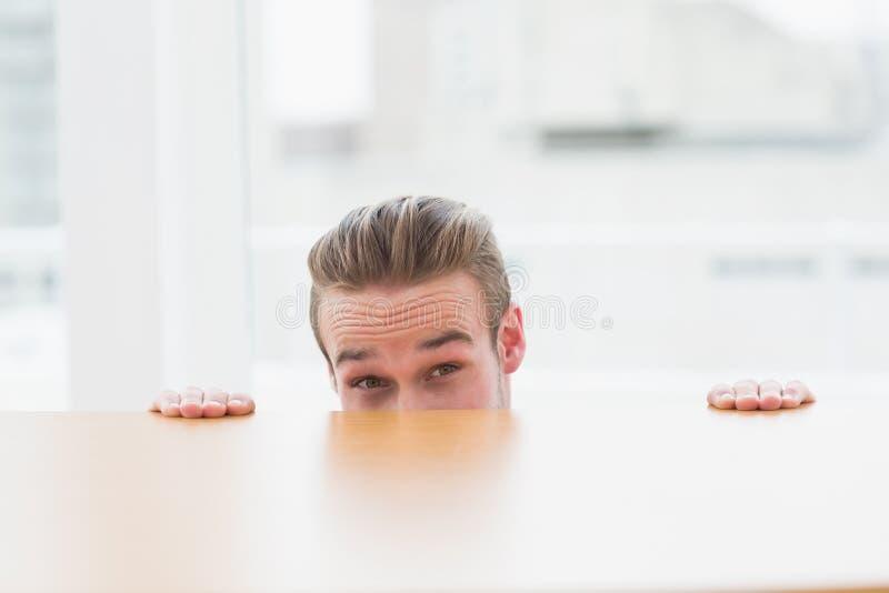 Nervous businessman peeking over desk royalty free stock photos