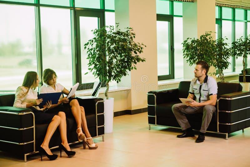 Nervous businessman sitting next to confident two businesswomen royalty free stock photos