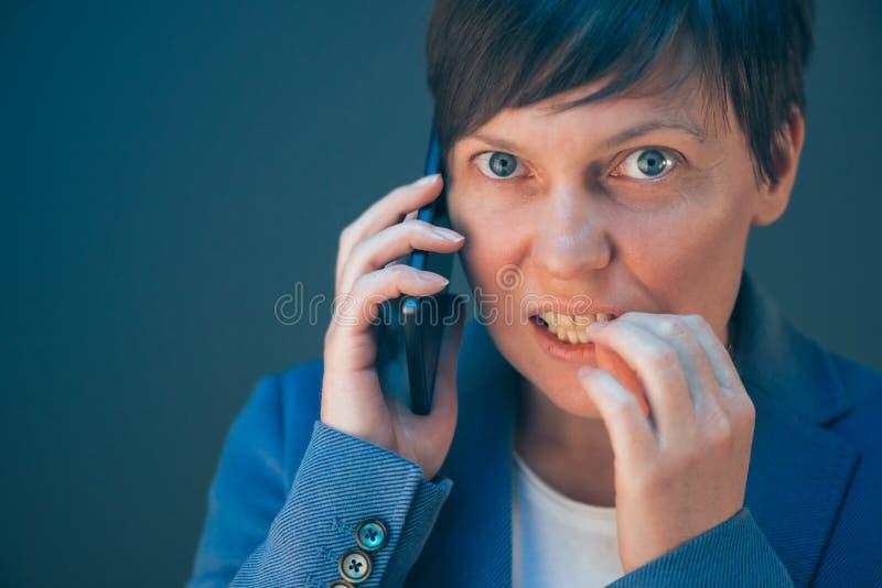 Nervous businesswoman bites fingernails during telephone conversation stock image